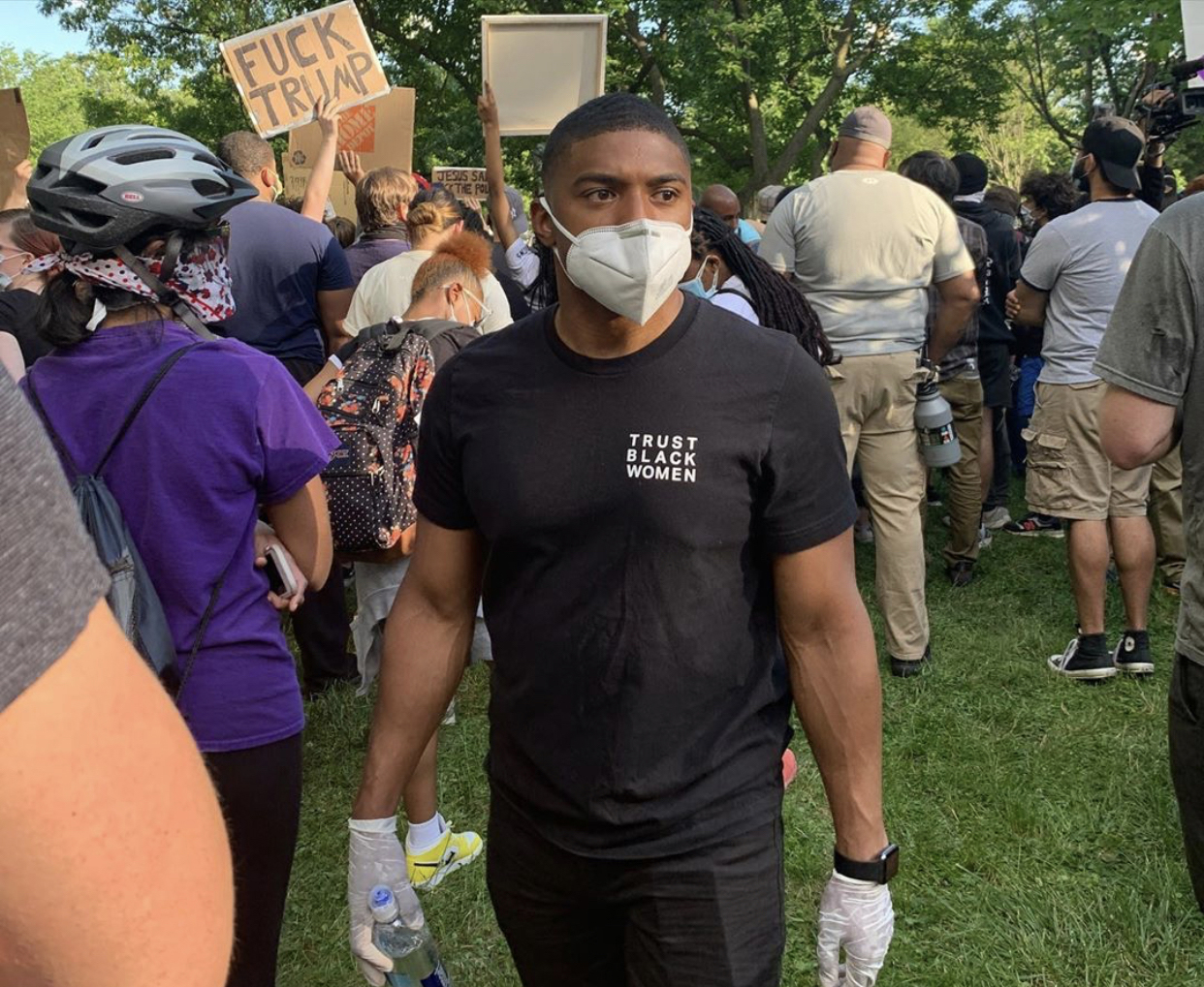BLM protestor in District of Clothing 'Trust Black Women' t-shirt.